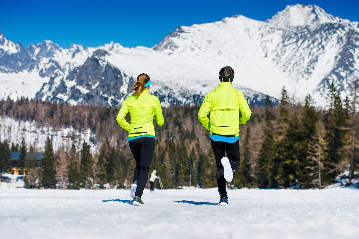 46625147 - young couple jogging outside in sunny winter mountains