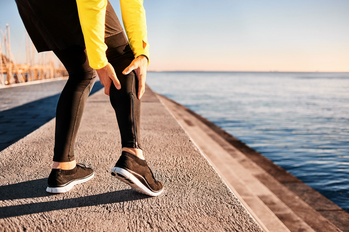 48258203 - muscle injury - athlete running clutching calf muscle after spraining it while out jogging on the beach near ocean. sports injury concept with running man outside